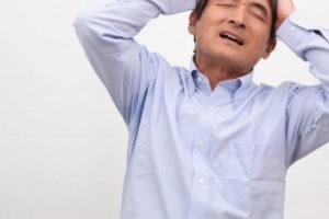 頭を抱えた男性。硬いパイプの枕は音がして眠れない、というイメージ